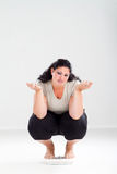 Unhappy overweight woman. An unhappy overweight woman crouching on scale checking her weight Royalty Free Stock Images