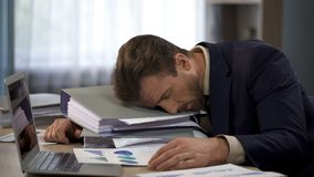 Unhappy overworked male manager lying on pile of folders at workplace, tiredness. Stock photo stock photography