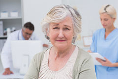 Unhappy patient with doctor and nurse working in background Royalty Free Stock Images
