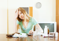Unhappy pensive woman counting the cost of medications Royalty Free Stock Image