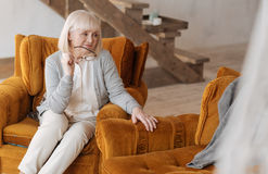 Unhappy pessimistic woman looking at the empty armchair. Now I am alone. Unhappy pessimistic aged woman sitting In the armchair and holding her glasses while Stock Image