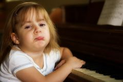 Unhappy piano player 1. A little girl not wanting to play the piano Stock Images