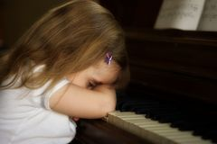 Unhappy piano player. A little girl not wanting to play the piano Royalty Free Stock Images