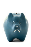 Unhappy piggy-bank isolated on white. Blue unhappy piggy bank isolated on white conceptual image Royalty Free Stock Image