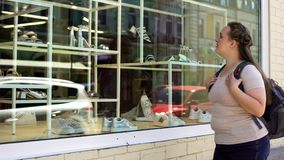 Unhappy poor female looking at shop window with shoes, expensive footwear. Stock photo stock image