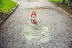 Unhappy, poor little girl sitting on asphalt with drawing sun. Royalty Free Stock Image