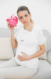 Unhappy pregnant woman shaking a piggy bank while touching her belly Stock Photos