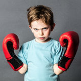 Unhappy preschooler with red hair showing his boxing gloves. Unhappy beautiful young male preschooler with freckles and red hair showing his boxing gloves up royalty free stock image