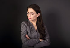 Unhappy resentful business woman in suit with folded arms lookin. G down on dark grey background Stock Photos