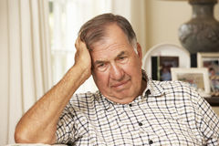 Unhappy Retired Senior Man Sitting On Sofa At Home Stock Photo