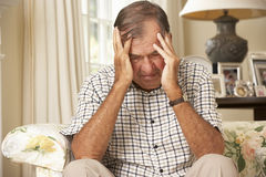 Unhappy Retired Senior Man Sitting On Sofa At Home Stock Photography