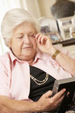 Unhappy Retired Senior Woman Sitting On Sofa At Home Looking At Photograph Royalty Free Stock Photo