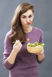 Unhappy 20s girl questioning the taste of a mixed green salad Stock Photography