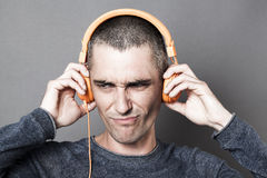Unhappy 30s man frowning in listening to noise or music. Painful sound concept - unhappy 30s man frowning in listening to noise or music on orange headphones Royalty Free Stock Photo