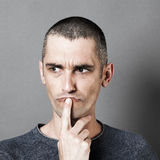 Unhappy 30s man having doubts, thinking and questioning. Portrait of unhappy 30s man having doubts, putting his index on his mouth to think and question,grey Stock Images