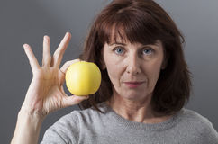 Unhappy 50s mature woman questioning the taste of golden apple Royalty Free Stock Photo