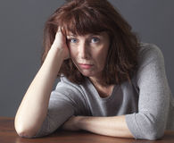 Unhappy 50's woman thinking about aging issues. Depressed mature woman resting her face on her hands laying down on a table for laziness or frustration Stock Photography