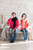 Unhappy sad couple suffering from flu. Unpleasant disease. Tired unhappy young couple sitting in the bedroom and wiping their noses while having flu Stock Photography