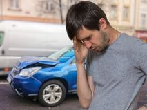 Unhappy sad driver had car accident. Destroyed car in background.  royalty free stock image