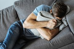 Unhappy sad man crying. Feeling helpless. Unhappy sad pleasant man lying on the sofa and putting his face in the cushion while crying Royalty Free Stock Image