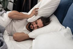 Unhappy sad man wanting to stay in bed longer. Why so early. Unhappy sad man wanting to stay in bed while hearing the sound of alarm clock royalty free stock images