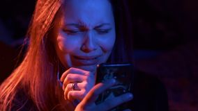 Unhappy sad teenage girl at night with phone reading sms. Highly expressive. stock video
