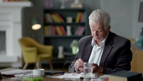 Unhappy sad and troubled elderly man incredulously looks at a pill.  stock video