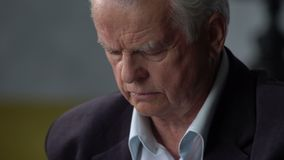 Unhappy sad and troubled elderly man looks at a pill and going to take it stock footage