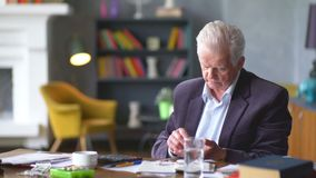 Unhappy sad and troubled elderly man looks at a pill and ponder stock video