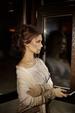 Unhappy sag lonely girl stand near the dark window and think about something. Lonely sad girl look out window and wait for call. P Royalty Free Stock Photos