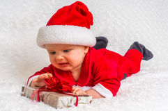 Unhappy Santa baby lying on white blanket with gift Stock Photography