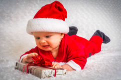 Unhappy Santa baby lying on white blanket with gift Stock Image
