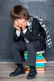 Unhappy school boy sitting on books Stock Images