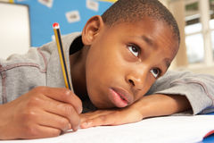 Unhappy Schoolboy Studying In Classroom royalty free stock image