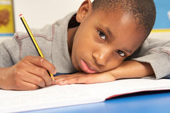 Unhappy Schoolboy Studying In Classroom Stock Photography