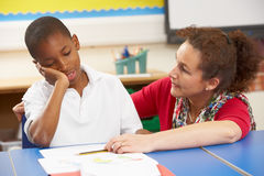 Unhappy Schoolboy Studying In Classroom. With Teacher Royalty Free Stock Photography