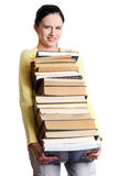 Unhappy schoolgirl holding pile of books. Royalty Free Stock Photos