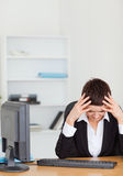 Unhappy secretary. In her office Royalty Free Stock Photography