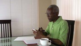 An unhappy senior citizen using a calculator to figure out his finances