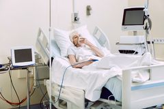 Unhappy senior lady with oxygen mask at hospital. Having no strength. Depressed retired woman lying in a hospital bed and holding her oxygen mask while stock images
