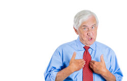 Unhappy senior man, executive, grandpa, pointing at himself as if to say, you mean me, you talking to me? Royalty Free Stock Photo