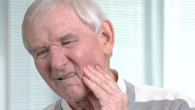 Unhappy senior man having toothache. Stressed elderly man with terrible toothache on blurred background close up stock footage