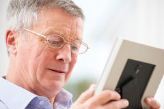 Unhappy Senior Man Looking At Photo In Frame Royalty Free Stock Photo