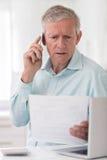 Unhappy Senior Man On Phone Querying Bill Royalty Free Stock Photos