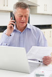 Unhappy Senior Man On Phone Querying Bill Royalty Free Stock Images