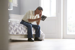 Unhappy Senior Man Sitting On Bed Looking At Photo Frame Stock Image