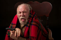 Unhappy senior man sticks out tongue Royalty Free Stock Photography