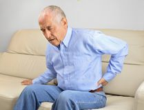 Senior man with Back pain. Unhappy senior man suffering back pain sitting on a sofa in the living room at home stock photo