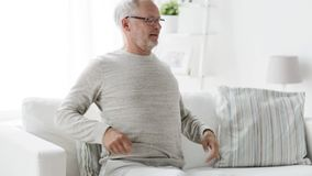 Unhappy senior man suffering from backache at home 132. People, healthcare and problem concept - unhappy senior man suffering from pain in back or reins at home stock footage