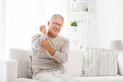 Unhappy senior man suffering elbow pain at home. People, healthcare and problem concept - unhappy senior man suffering from elbow pain at home Royalty Free Stock Image
